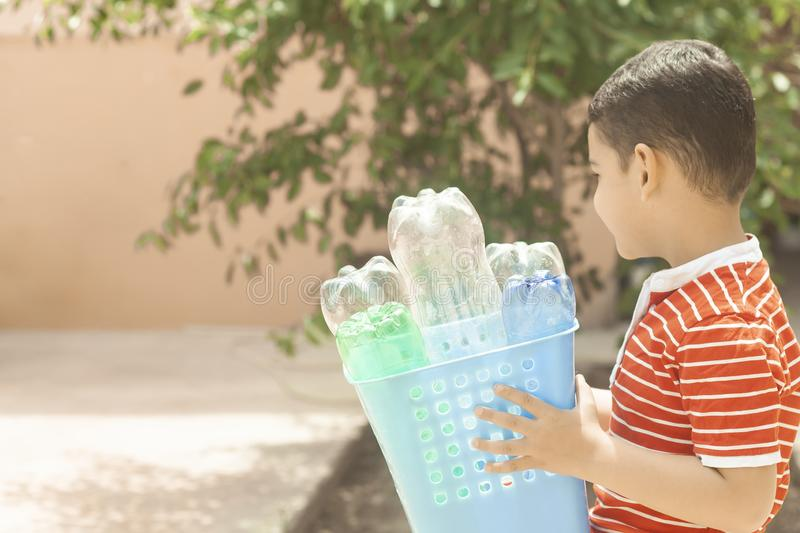 Plastic pollution. Little boy collected plastic bottles and holding recycling bin. Free space. Plastic pollution. Little boy collected plastic bottles and stock image