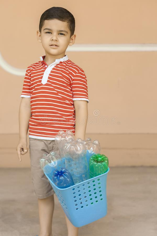 Plastic pollution. Little boy collected plastic bottles and holding recycling bin. Free space. Plastic pollution. Little boy collected plastic bottles and stock photo