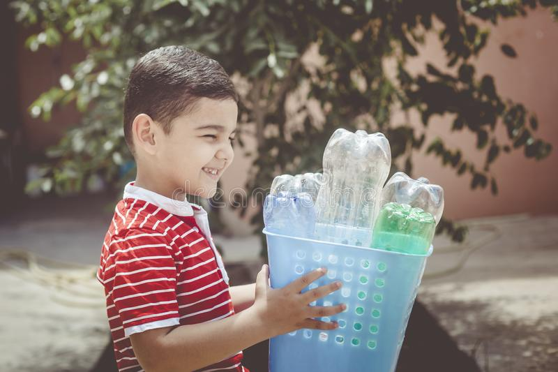 Plastic pollution. Little boy collected plastic bottles and holding recycling bin. Free space. Plastic pollution. Little boy collected plastic bottles and royalty free stock photography