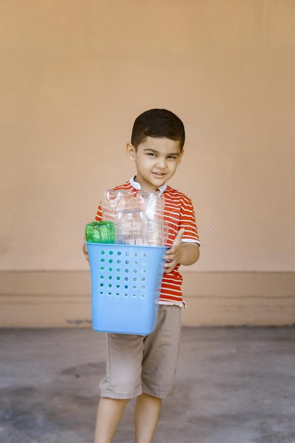 Plastic pollution. Little boy collected plastic bottles and holding recycling bin. Free space. Plastic pollution. Little boy collected plastic bottles and royalty free stock image