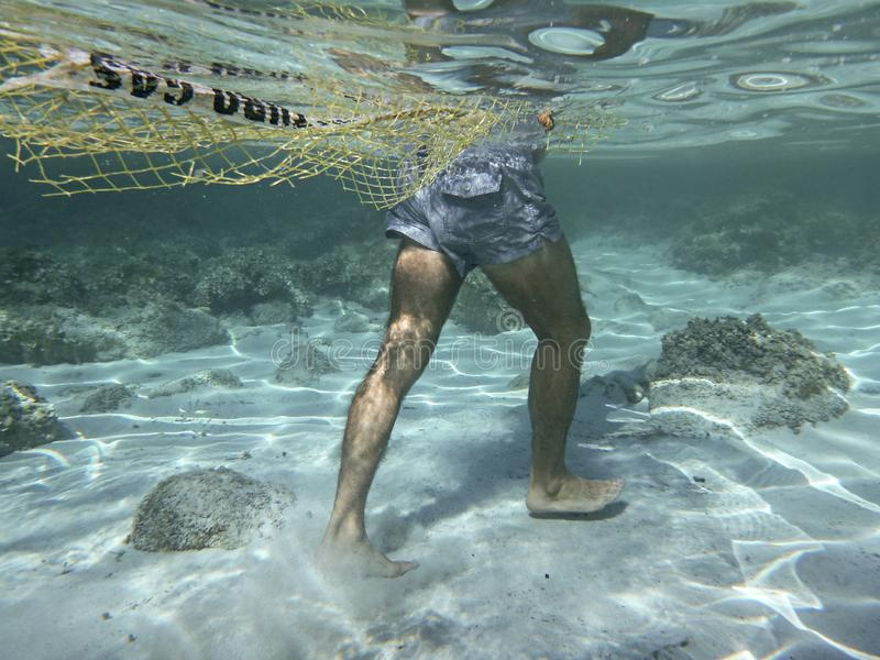 Plastic pollution in the ocean and in the sea: underwater shot of a man walking on the seabed dragging a fishing net and a piece stock photo