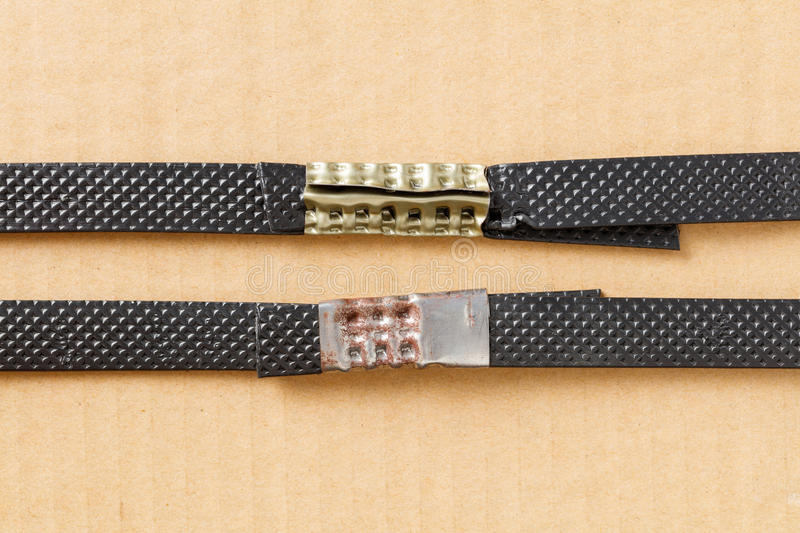 Plastic poly strap with metal clamp. Close up plastic poly strap with metal clamp on carton or cargo box royalty free stock image