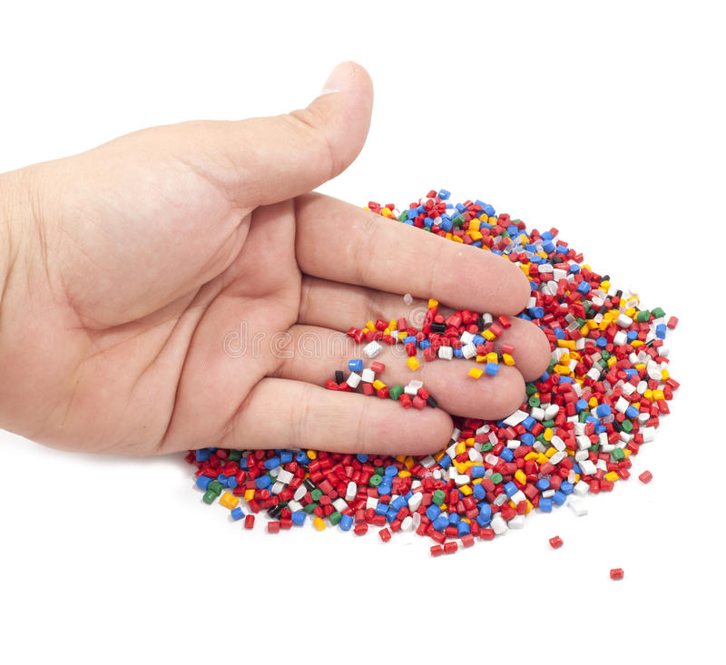 Plastic polymer granules. Colorful plastic polymer granules and man hand on white background royalty free stock photography