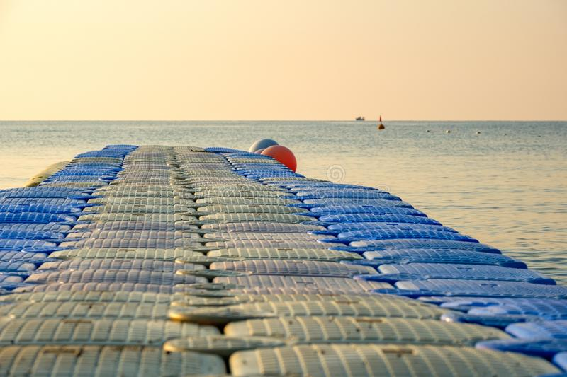 Plastic pontoon on the sea going into the distance for swimming. In the background a lone ship out of focus stock photo