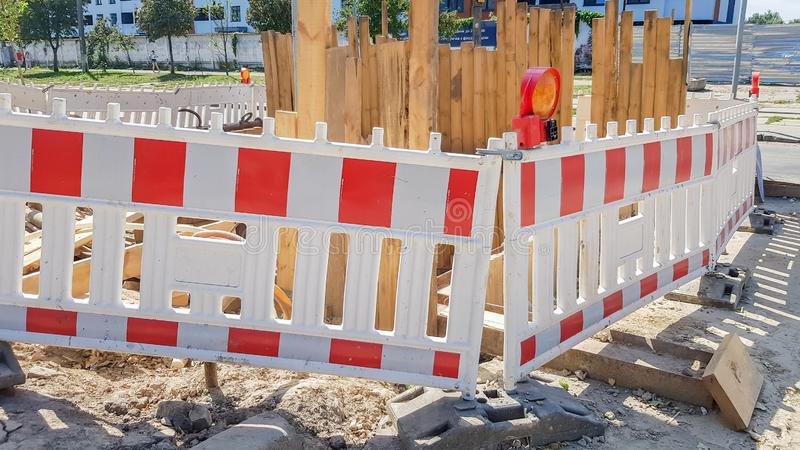 Plastic Protective barrier fences the site of road work. Red and white plastic fence near the street repair site. Construction royalty free stock photo