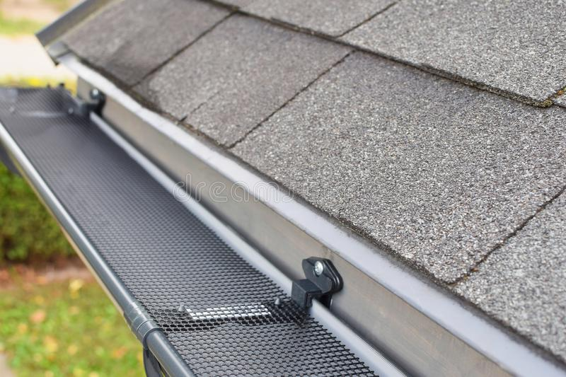 Plastic rain gutter. Plastic guard over new dark grey plastic rain gutter on asphalt shingles roof at shallow depth of field royalty free stock photos