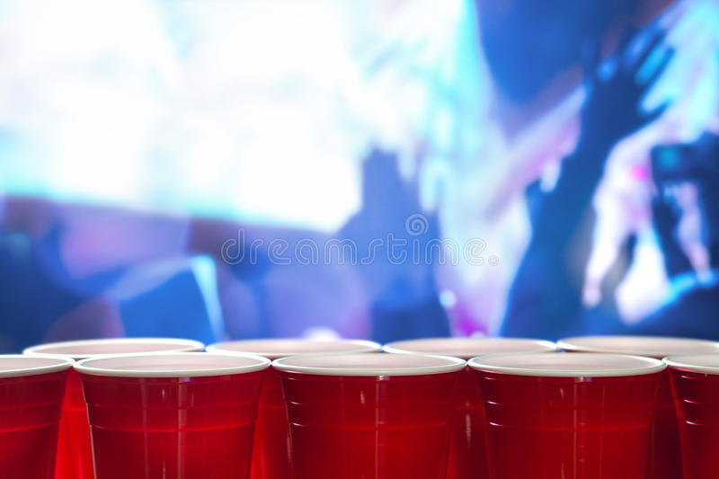 Plastic red party cups in a row in a nightclub full of people dancing on the dance floor in the background. Perfect for marketing and promotion for events or royalty free stock photo