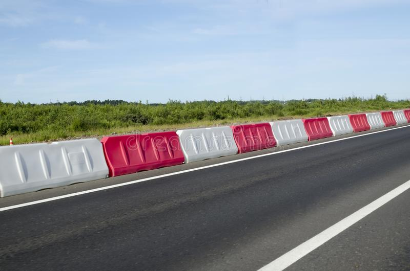 Plastic red and white fences on the road on the highway, on the ring road in the modern city. roadside signs for car drivers. Dividing strip stock image