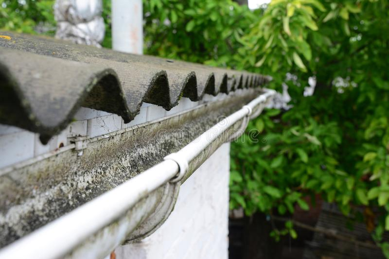 Plastic roof guttering, rain guttering & drainage with old asbestos roof. royalty free stock photos