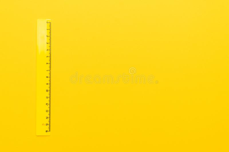 Yellow plastic ruler on the yellow background royalty free stock photo