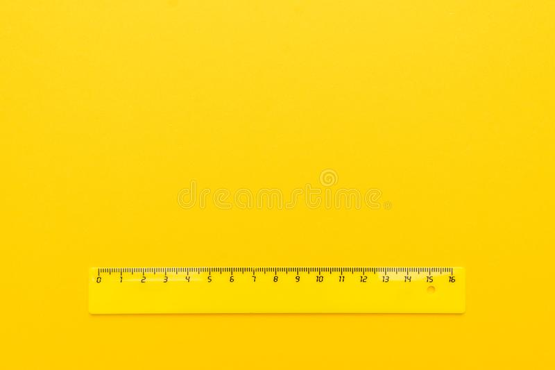 Yellow plastic ruler on the yellow background stock images