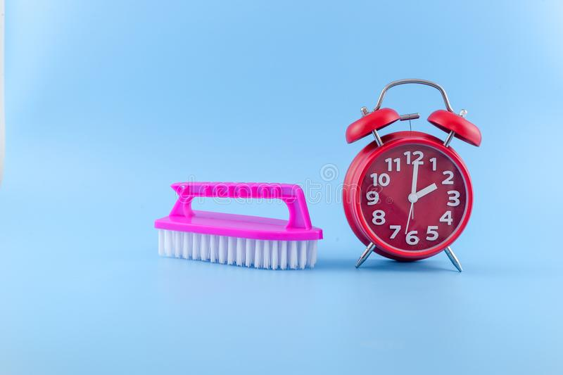 Plastic Scrub Brush With red alarm Clock on blue background royalty free stock photo