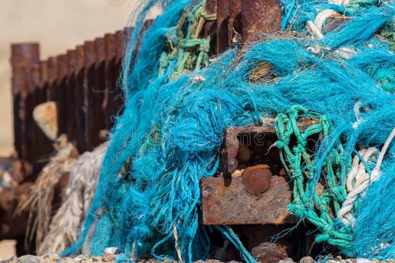 Plastic sea pollution. Tangled nylon fishing net caught up on a. Dangerous plastic sea pollution. Tangled nylon fishing net washed up and caught on a rusty beach stock image