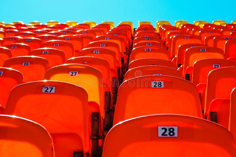 Plastic seats on the sports platform of the stadium against the sky. Bright empty plastic seats on the sports platform of the stadium against the blue sky royalty free stock photography
