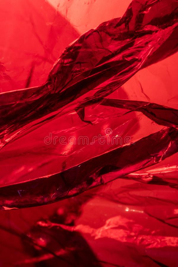 Plastic Shiny See Through Abstract Shimmer Creased Background. Red crumpled dark stock image