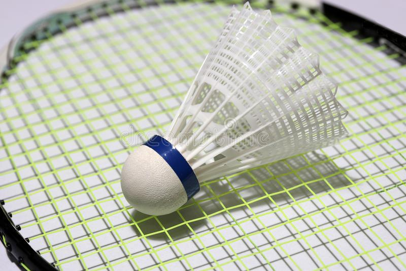 Plastic shuttle van badminton gezet op het groene net van badmintonracket stock foto's