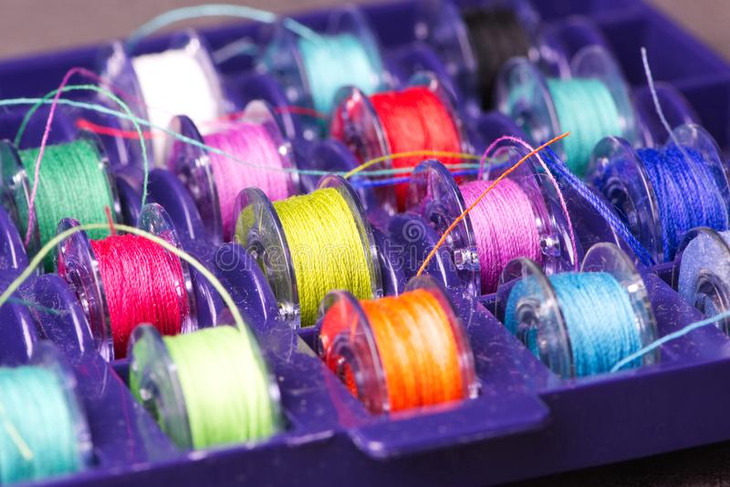 Plastic spools with colored yarn. Box with plastic spools with colored polyester yarn on it, close up photo stock image
