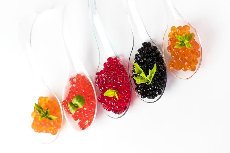 Plastic spoons with fish caviar stock images