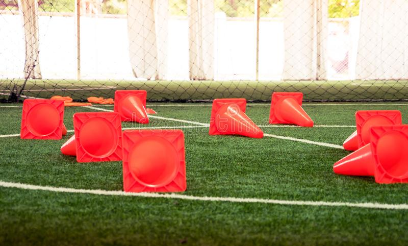 Plastic sport training cone on soccer field. Plastic sport training cone on indoor soccer field royalty free stock images