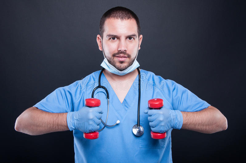 Plastic surgeon making exercises with dumbbells and smiling stock images
