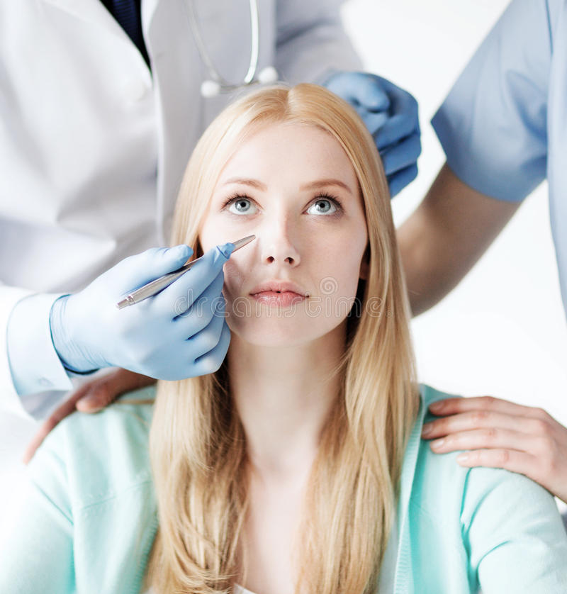 Plastic surgeon and nurse with patient royalty free stock photo