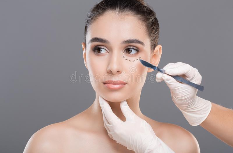 Plastic surgeon preparing woman for beauty procedures. Marking her face with pencil, gray background royalty free stock photo
