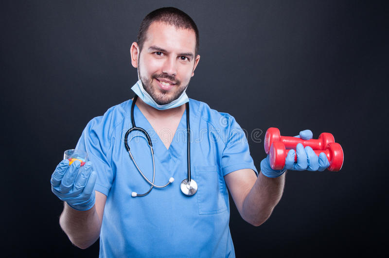 Plastic surgeon wearing scrubs holding dumbbell and pills royalty free stock photography
