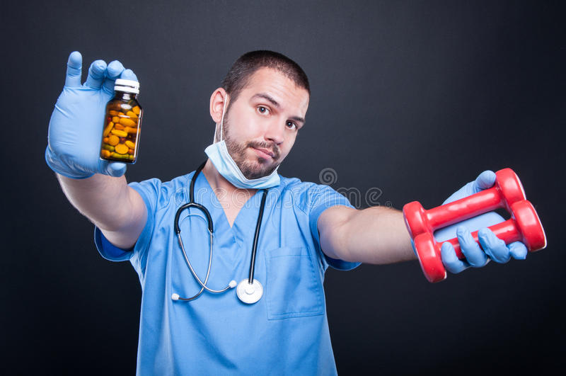 Plastic surgeon wearing scrubs showing dumbbells and pills royalty free stock photography