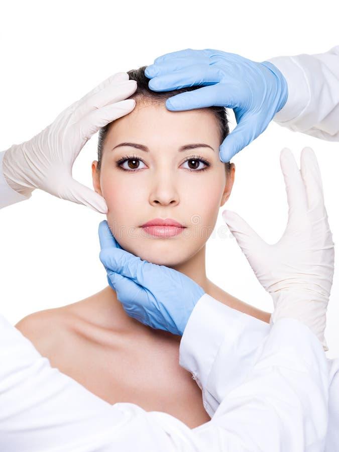 Plastic surgeons touching female face stock images