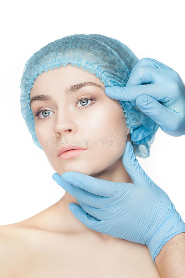 Plastic surgery concept. Doctor hands in gloves touching woman face. Plastic surgery concept. Doctor hands in gloves touching the beautiful woman face on white stock photo