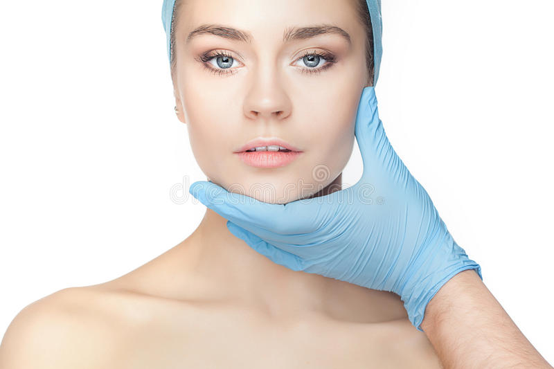 Plastic surgery concept. Doctor hands in gloves touching woman face stock images