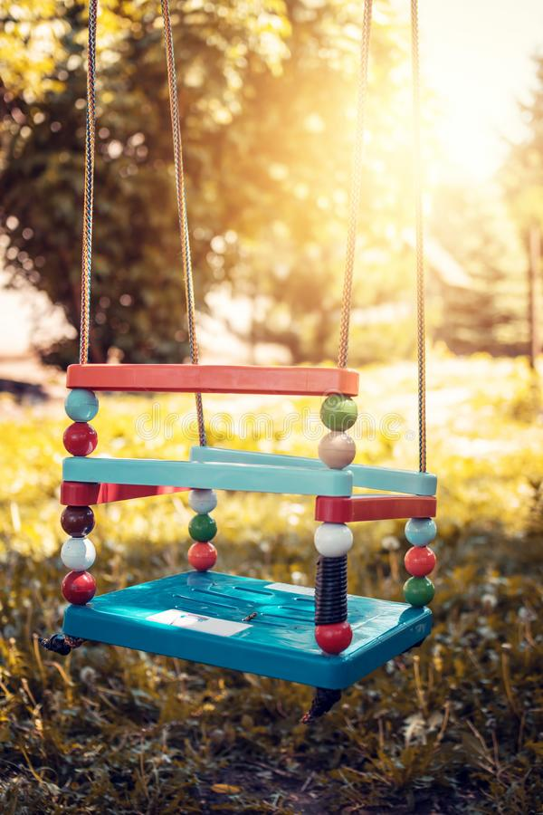 Plastic swing in the park. Colorful plastic swing in the park royalty free stock image