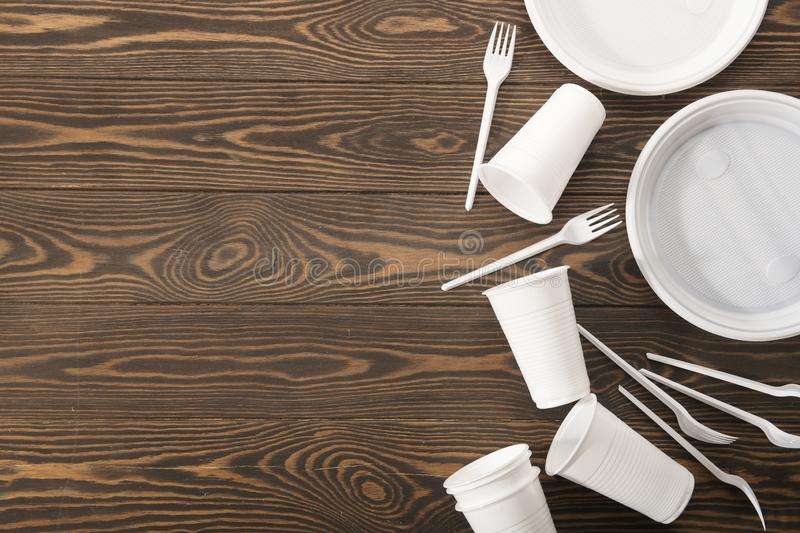 Plastic tableware on wooden background. Secondary processing. The concept of zero waste. royalty free stock photos
