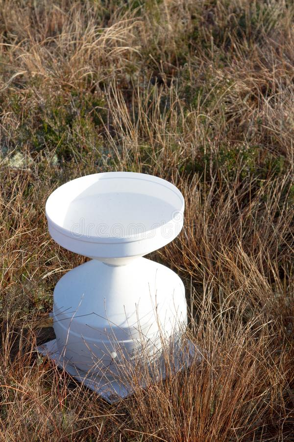A plastic tipping bucket rain gauge stock photography