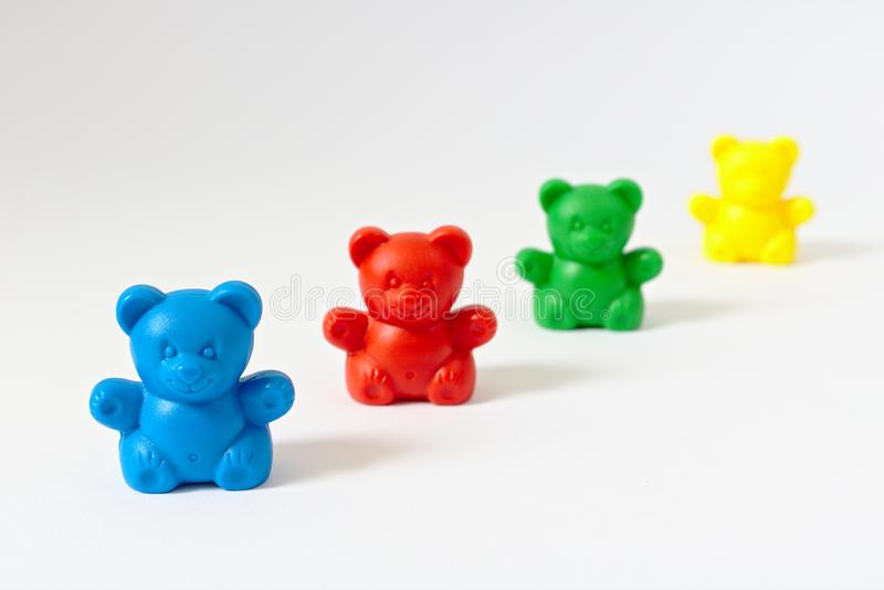 Plastic toy bears on white in different colors forming a line which disappears into the background. Plastic toy bears on white in different colors blue, red stock images
