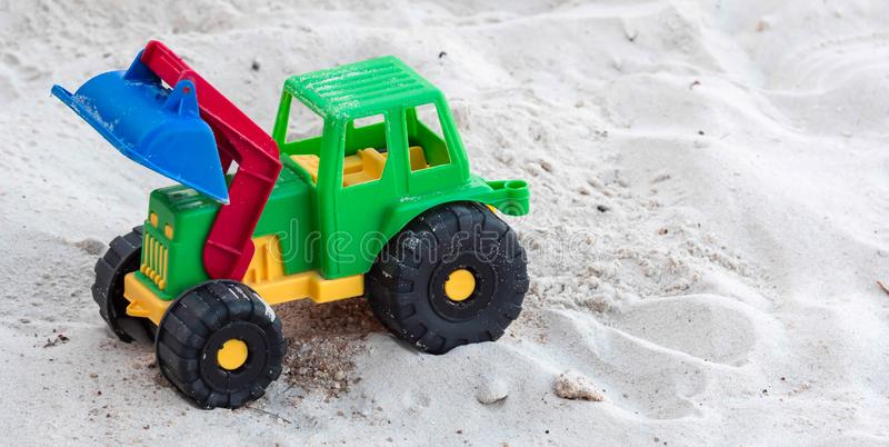 A plastic toy bulldozer color green, red, yellow and blue with black big wheels placed on a white sand in a beach resort royalty free stock image