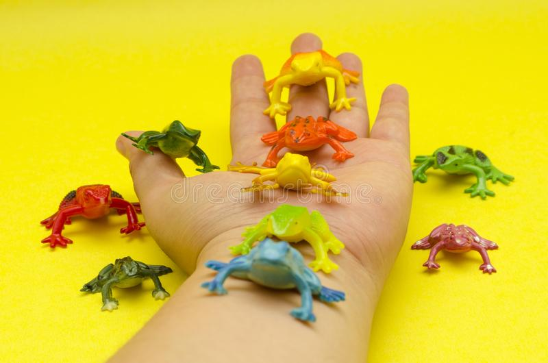 Plastic toy frogs on a hand against yellow background stock photos