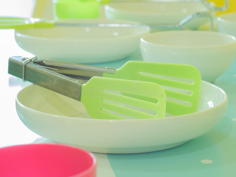 Plastic toy kitchen utensils and tableware toys on a table royalty free stock photos
