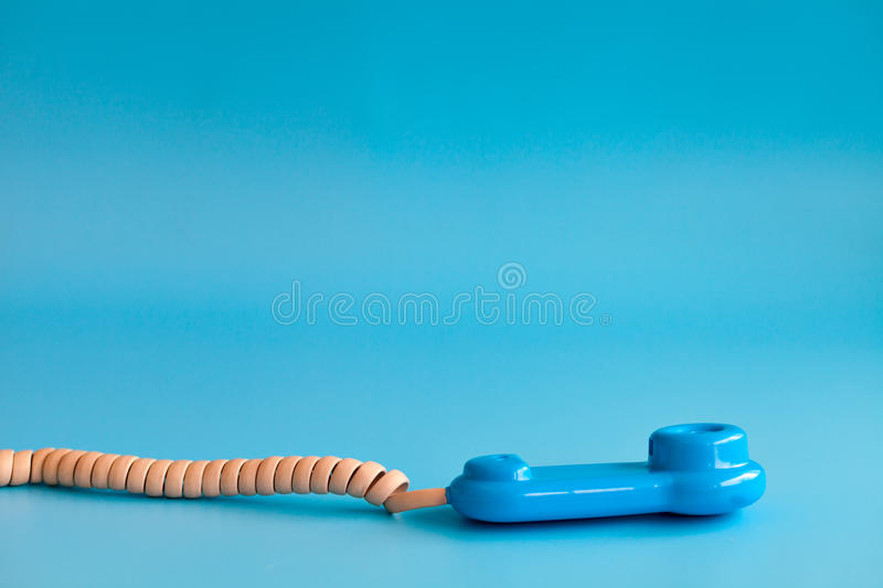 Plastic toy mobile phone on a blue background stock photography