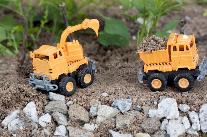 Loading and digging and Dump truck. Plastic toy orange color for construction. by Loading and digging and Dump truck. with nature and road simulator for royalty free stock images