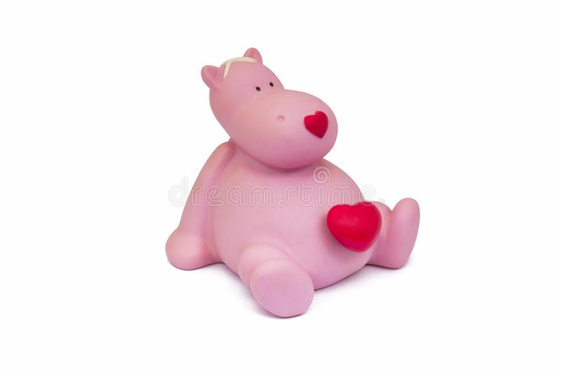 Plastic toy pink hippo with red heart sitting isolate on white background stock photos