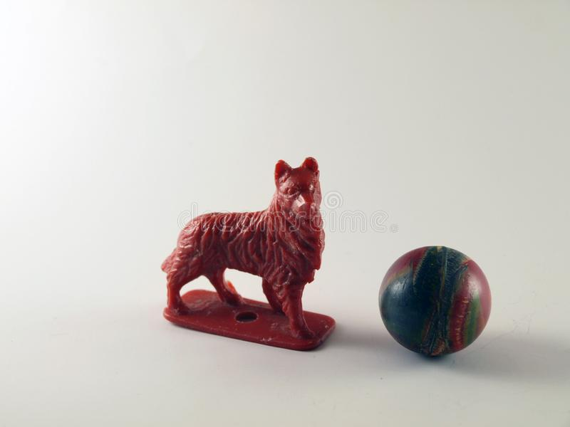 A  Plastic Toy Red Dog and a Colorful Rubber Ball stock photo