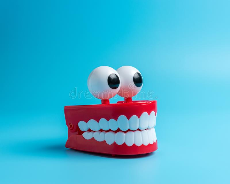 Plastic toy teeth on blue background. Abstract minimal composition royalty free stock image