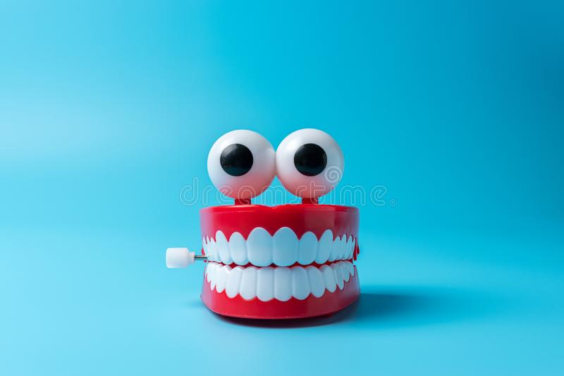Plastic toy teeth on blue background. Abstract minimal composition royalty free stock photo