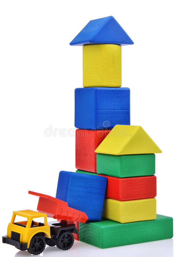 Plastic toy truck with wooden cubes tower. Building process stock photo