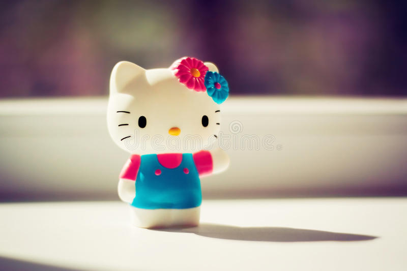 Plastic toy of a white kitty in home. Interior royalty free stock photo