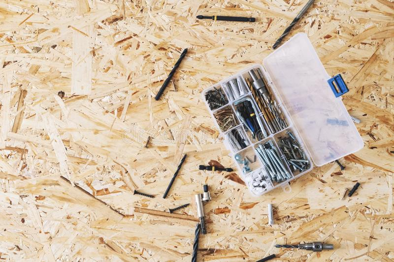 Plastic transparent organizer with screws, dowels, drills, bits on the background of the OSB. royalty free stock photo