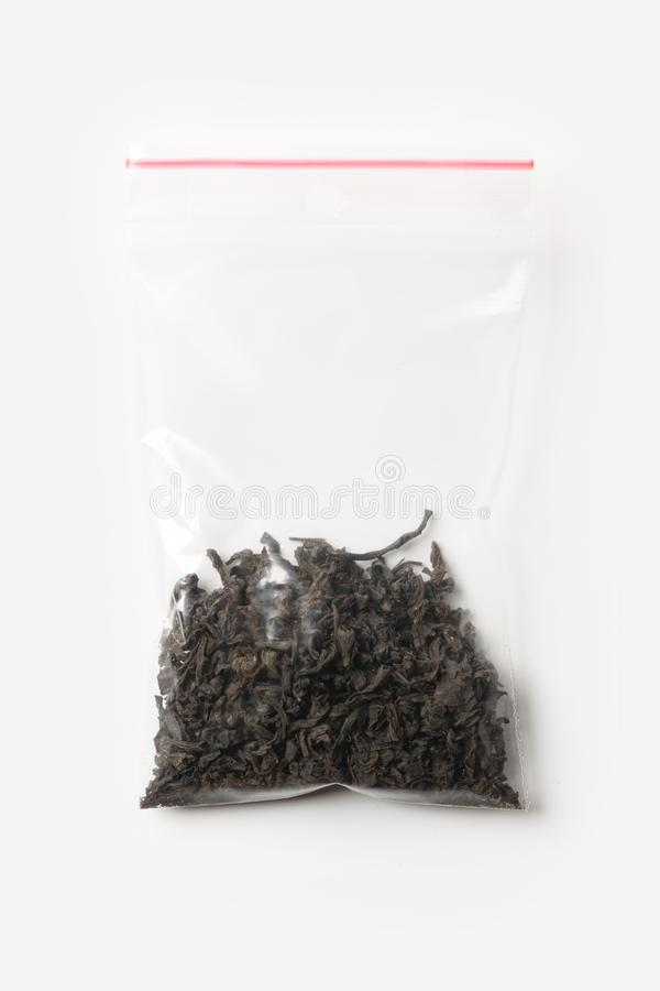Plastic transparent zipper bag with a little black tea isolated on white, Vacuum package mockup with red clip. Concept. royalty free stock photography