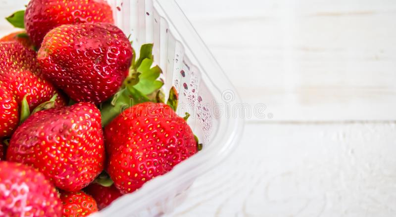 Plastic tray with red strawberries on a white wooden background stock images