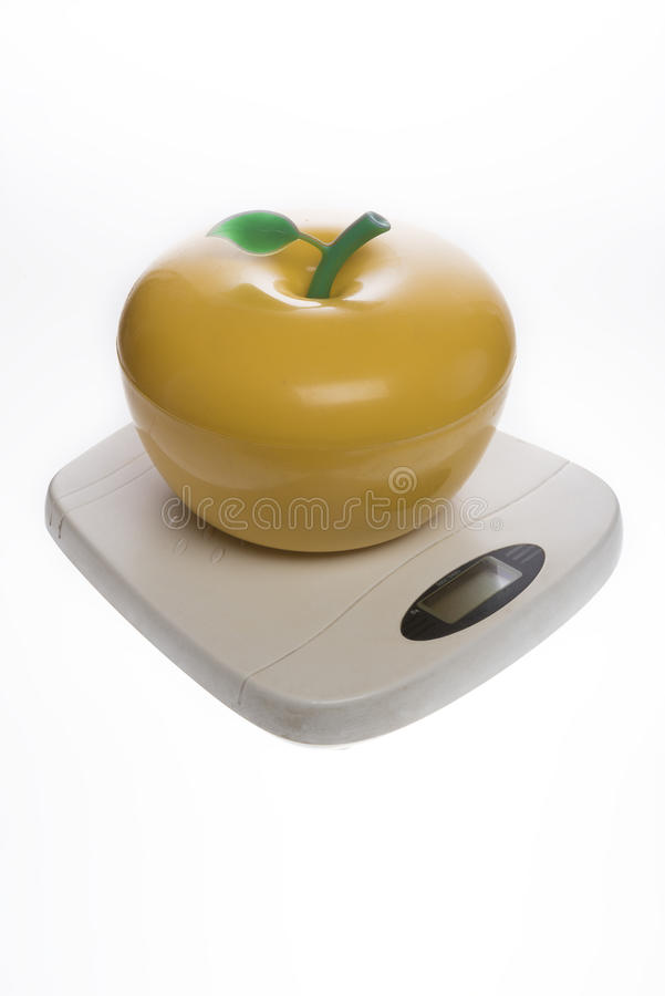 Plastic vase in the form of a yellow apple on the scales. Plastic vase in the form of a yellow apple on household floor scales royalty free stock photo